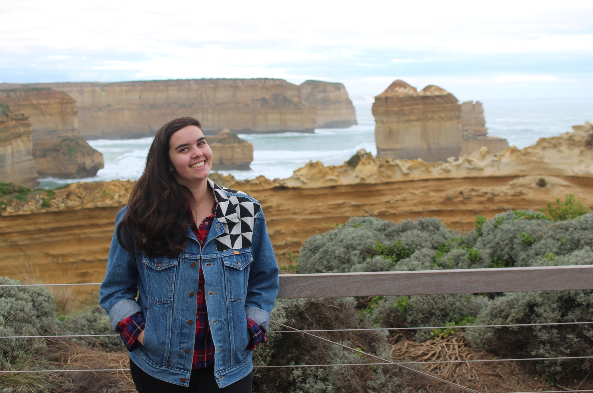 Beth standing in front of cliffs and the ocean in Australia.
